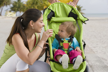 Hispanic woman checking on baby in jogging stroller