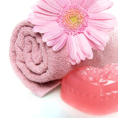 a towel, soap and a flower
