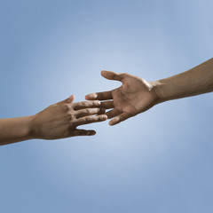 Mixed race people reaching out hands toward one another