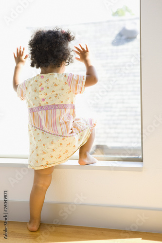 Mixed race girl looking out window