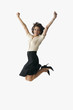 Hispanic businesswoman cheering and jumping in air