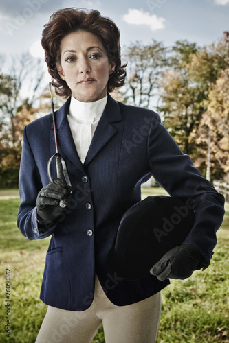 Hispanic woman wearing riding gear holding hat and crop