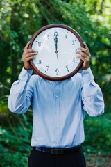 Hispanic businessman holding clock in forest