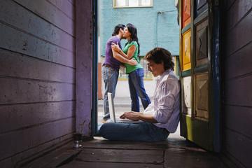 Hispanic man using laptop in doorway with couple in street beyond