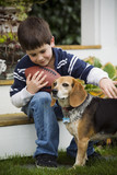 Mixed race boy with football petting dog