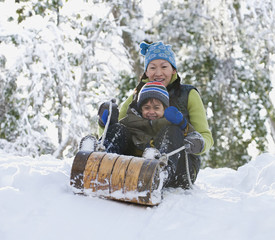 Asian mother and son riding on sled