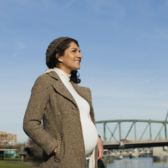 Pregnant Middle Eastern woman standing at waterfront
