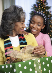 African girl giving grandmother Christmas gift