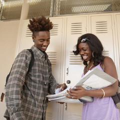 African teenage couple talking in school hallway