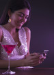 Hispanic woman text messaging in nightclub