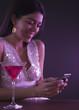 Hispanic woman text messaging in nightclub