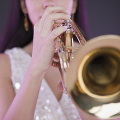 Hispanic woman playing trumpet