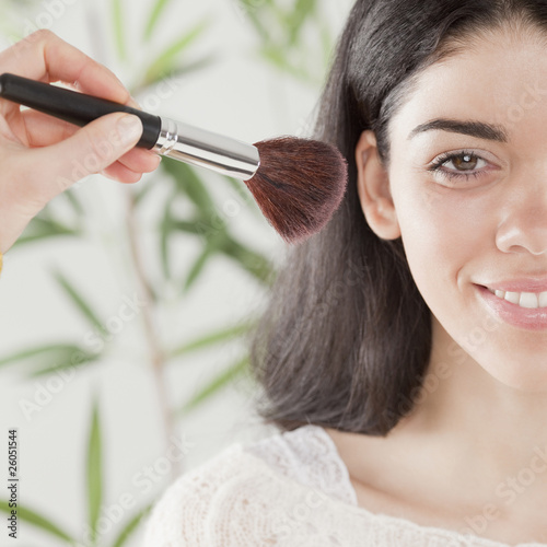 Hispanic woman applying blush