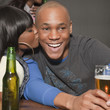 African woman kissing boyfriend in bar