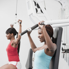 African woman using weight machines in health club