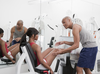 African man helping woman on exercise equipment