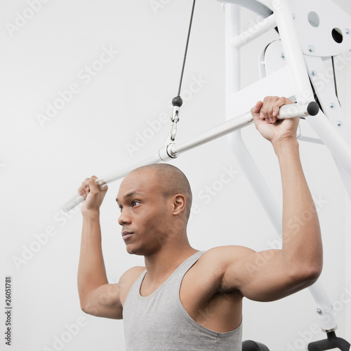African man using weight machine in health club