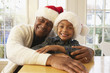 African grandfather and grandson wearing Santa hats