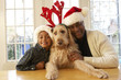 African grandfather and grandson wearing Santa hats and dog in antlers