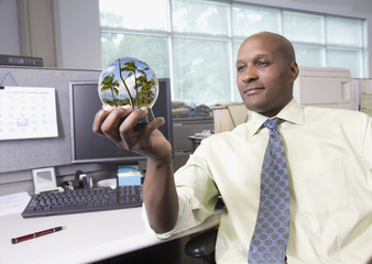 African businessman viewing vacation in snow globe