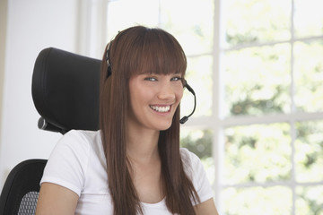 Pacific Islander woman using headset