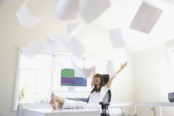Pacific Islander woman throwing papers in office