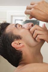 Hispanic man using eye drops