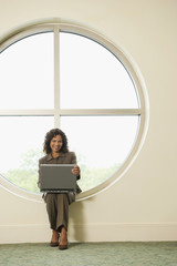 Hispanic businesswoman typing on laptop in office