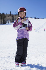 Mixed race girl showing off skiing medal