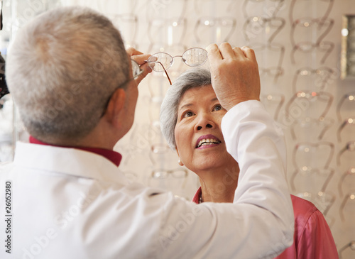 Chinese optician fitting womanÕs eyeglasses