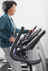 African woman using treadmill in health club