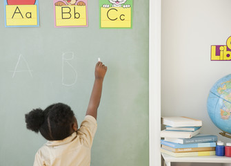 African girl writing on blackboard