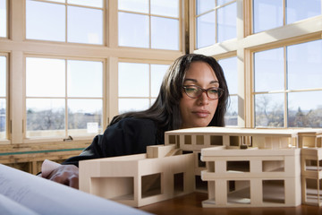 Mixed race architect looking at building model