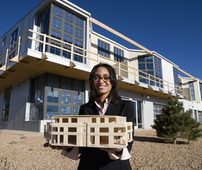 Mixed race architect holding building model