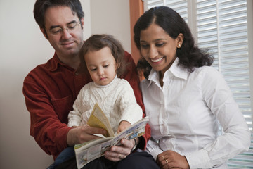Parents reading book to daughter