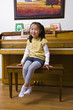 Korean girl sitting on piano bench