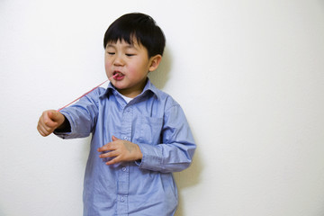 Korean boy pulling gum from mouth