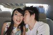 Chinese man kissing girlfriend in back of car