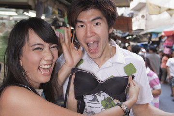 Asian woman holding up bra to boyfriend