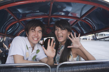 Asian couple in taxi waving