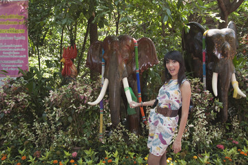 Asian woman holding tusk of elephant tusk