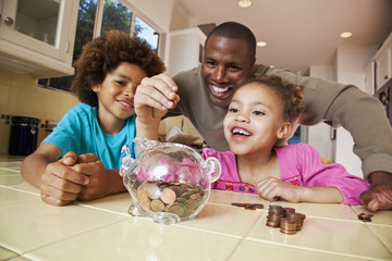 African father watching daughter put pennies into piggy bank