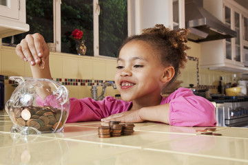 African girl putting pennies into piggy bank