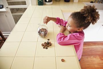 African girl putting pennies into piggy bank