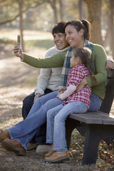 Hispanic woman taking family photo with cell phone