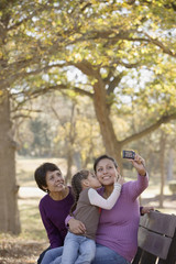 Hispanic woman taking family self-portrait with camera