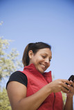 Hispanic woman text messaging on cell phones