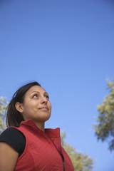 Hispanic woman looking up at sky