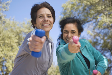 Hispanic women exercising with hand weights