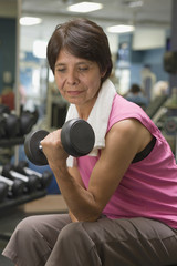 Hispanic woman exercising in health club